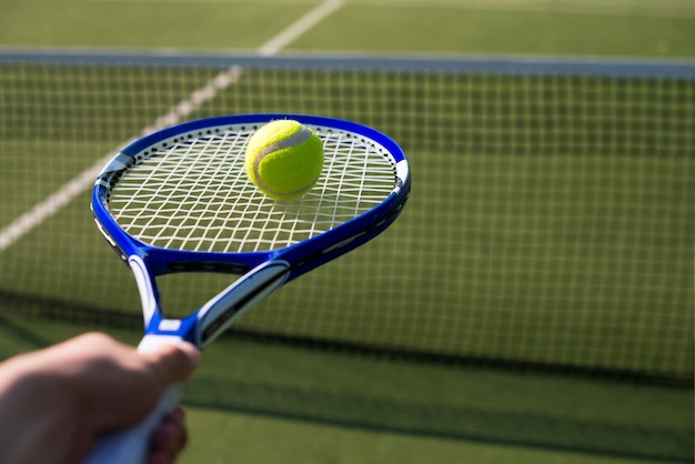 Close-up tennis racket with ball