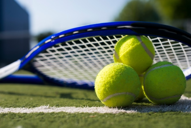 Close-up tennis rocket over balls