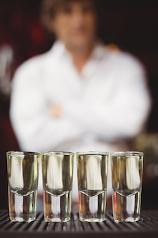 Close-up of tequila in shot glasses on bar counter