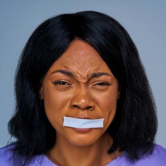 흰색 줄무늬로 봉인 된 입으로 겁에 질린 여성의 얼굴을 클로즈업합니다. 감정 개념