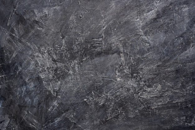 Close up texture background of black color painting on cement wall.