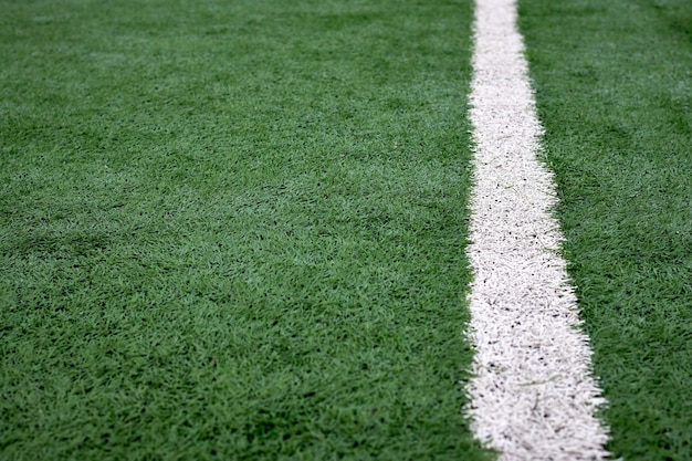 Close up texture of football field with white stripes, green artificial coating.