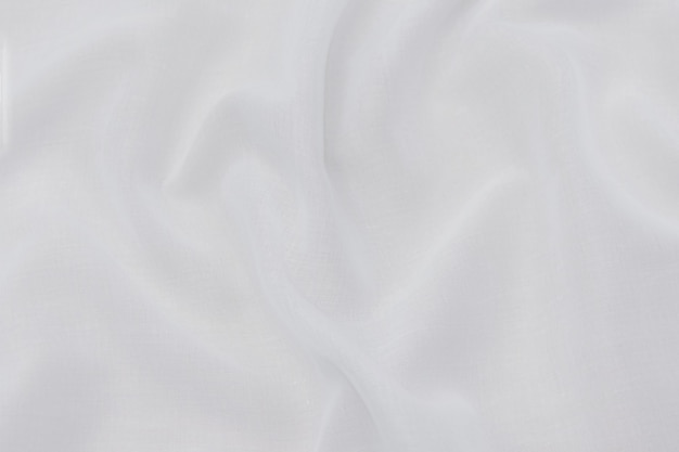 Close-up texture of natural beige or ivory or white fabric or cloth. fabric texture of natural cotton or linen or silk textile material. bright color canvas background.