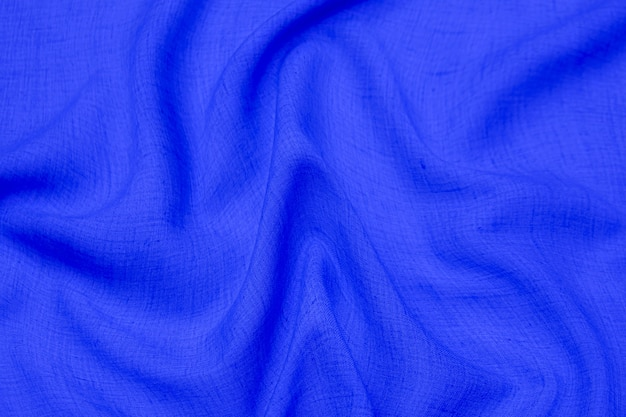 Close-up texture of natural blue fabric or cloth in same color. fabric texture of natural cotton or silk or wool textile material. blue canvas background.