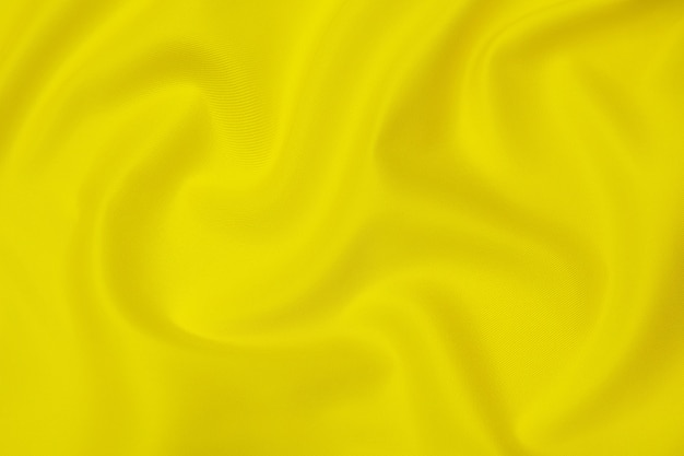 Close-up texture of natural orange or yellow fabric or cloth in same color. fabric texture of natural cotton, silk or wool, or linen textile material. yellow canvas background.