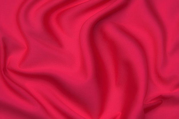 Close-up texture of natural red or pink fabric or cloth in same color. fabric texture of natural cotton, silk or wool, or linen textile material. red and orange canvas background.
