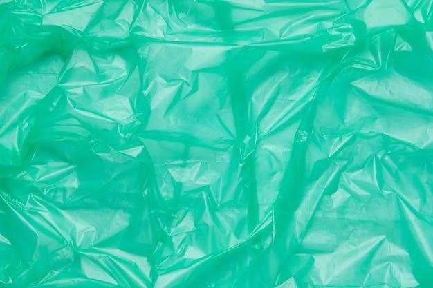 緑のプラスチックゴミ袋のテクスチャをクローズアップ。緑のポリエチレンフィルム
