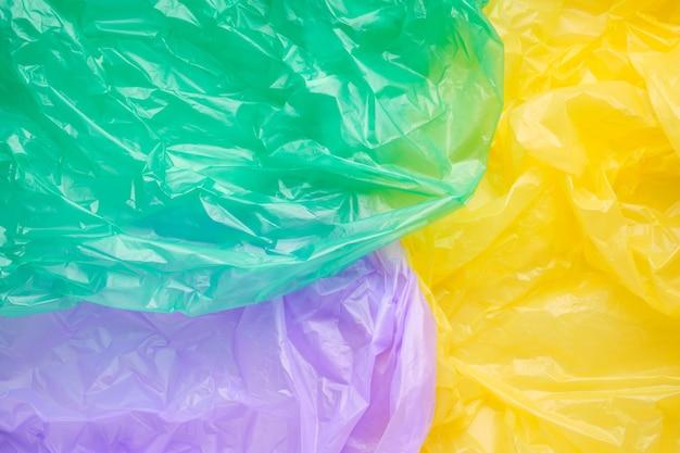 多色プラスチックゴミ袋のテクスチャをクローズアップ。緑のポリエチレンフィルム