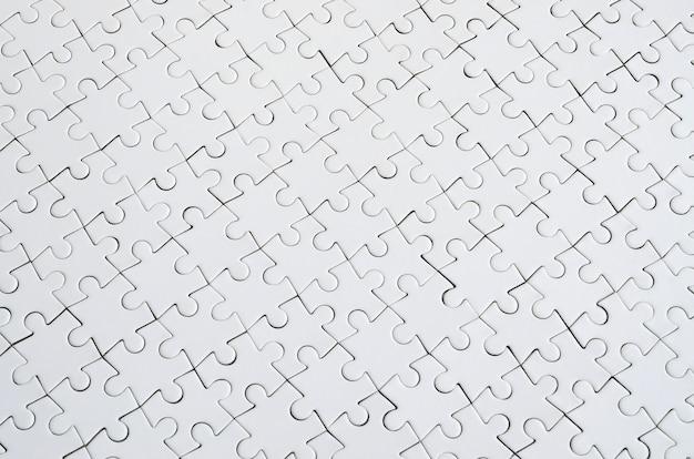 組み立てた状態で白いジグソーパズルのテクスチャを閉じる。上面図。大きな全モザイクの多くの要素が結合されています