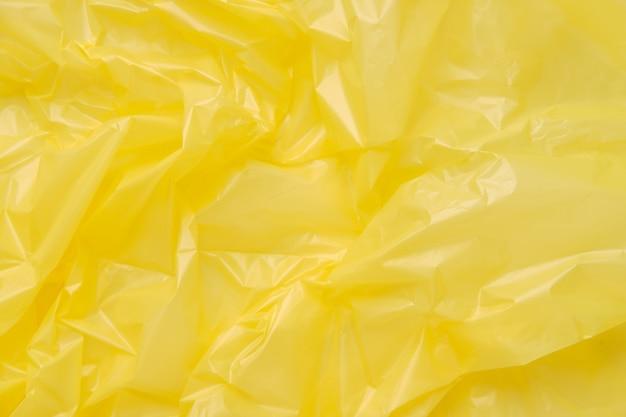 黄色いプラスチックのゴミ袋のテクスチャを閉じます。黄色のポリエチレンフィルム