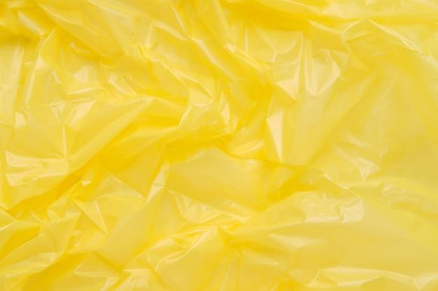 黄色いプラスチックのゴミ袋のテクスチャをクローズアップ
