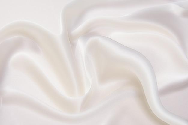 乳白色のナチュラルベージュまたはアイボリーの生地または布のクローズアップテクスチャ。天然コットンまたはリネンテキスタイル素材の生地の質感。アイボリーのキャンバスの背景。