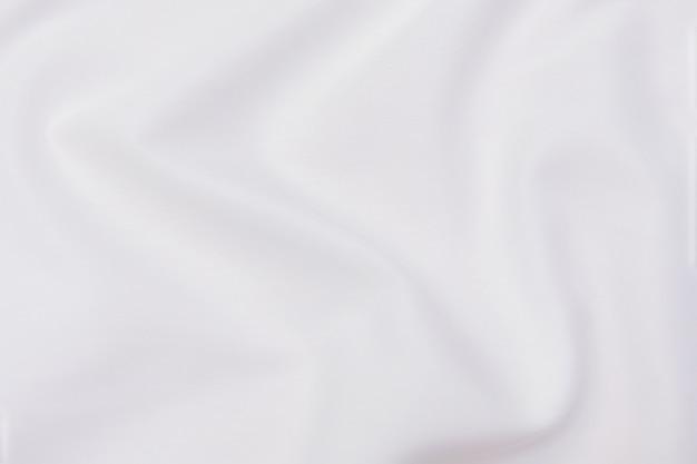 천연 베이지 또는 아이보리 또는 흰색 천이나 천의 클로즈업 질감. 천연 면이나 린넨 또는 실크 직물 소재의 패브릭 질감. 밝은 색상 캔버스 배경입니다.
