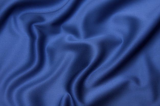 Крупный план текстуры натуральной синей ткани или ткани того же цвета. фактура ткани из натурального хлопкового или шелкового или шерстяного текстильного материала. фон синий холст.