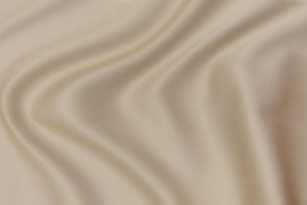 ナチュラルブラウンまたはベージュの生地または同色の布のクローズアップテクスチャ。天然コットン、シルク、ウール、またはリネンのテキスタイル素材の生地の質感。茶色のキャンバスの背景。