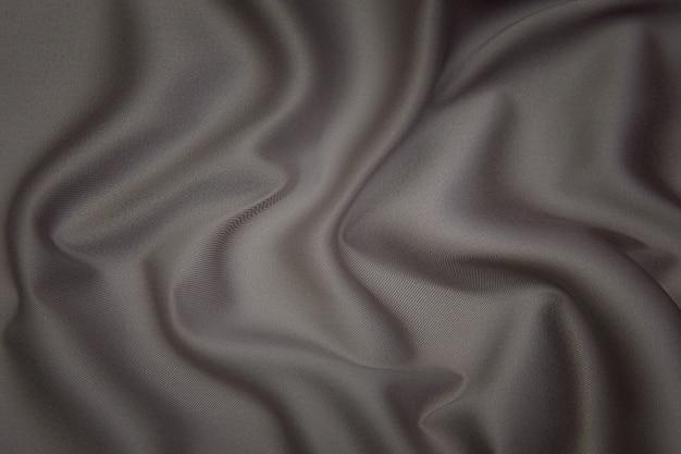 Крупный план текстуры натуральной коричневой или серой ткани или ткани того же цвета. фактура ткани из натурального хлопка, шелка или шерсти или льняного текстильного материала. предпосылка холста ткани.