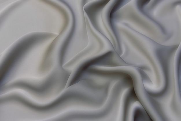 ナチュラルグレーの生地またはグレー色の布のクローズアップテクスチャ。天然コットンまたはリネンテキスタイル素材の生地の質感。灰色のキャンバスの背景。