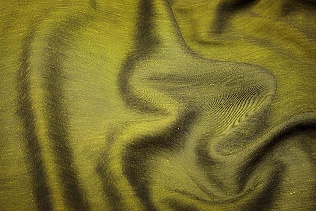 Крупный план текстуры натуральной зеленой или коричневой ткани или ткани того же цвета. фактура ткани из натурального хлопка, шелка или шерсти или льняного текстильного материала. цвет фона холста.