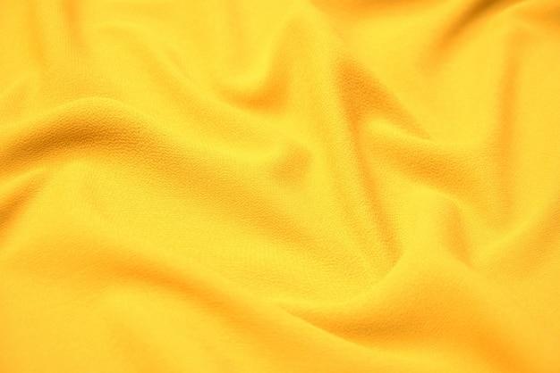 Крупный план натуральной оранжевой или желтой ткани или ткани того же цвета. фактура ткани из натурального хлопка, шелка или шерсти или льняного текстильного материала. желтый фон холст.