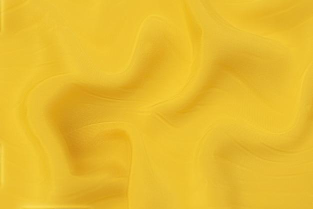 同じ色の天然オレンジまたは黄色の布または布のクローズアップテクスチャ。天然コットン、シルク、ウール、またはリネンのテキスタイル素材の生地の質感。黄色のキャンバスの背景。