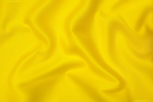 같은 색상의 천연 주황색 또는 노란색 천이나 천의 클로즈업 질감. 천연 면, 실크 또는 양모 또는 린넨 섬유 소재의 패브릭 질감. 노란색 캔버스 배경입니다.