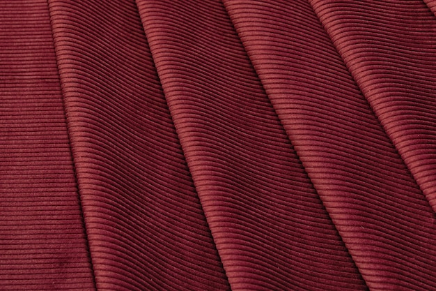 同じ色の天然の赤またはバーガンディの生地または布のクローズアップテクスチャ。天然コットン、シルク、ウール、またはリネンのテキスタイル素材の生地の質感。赤とオレンジ色のキャンバスの背景。