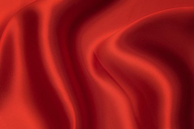 Крупный план текстуры натуральной красной или бордовой ткани или ткани того же цвета. фактура ткани из натурального хлопка, шелка или шерсти или льняного текстильного материала. красный и оранжевый фон холста.
