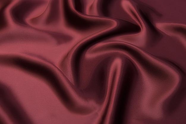 Крупный план текстуры натуральной красной или бордовой ткани или ткани того же цвета. фактура ткани из натурального хлопка, шелка или шерсти или льняного текстильного материала. фон красный холст.