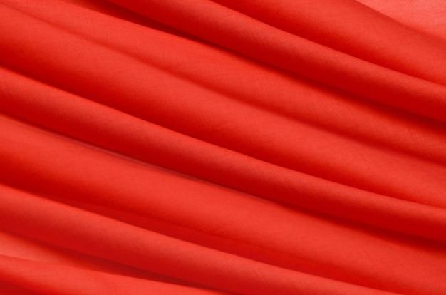 ナチュラルレッド、クリムゾン、ピンクの生地のクローズアップテクスチャ。天然コットン、シルク、ウール、またはリネンのテキスタイル素材の生地の質感。赤とオレンジ色のキャンバスの背景。