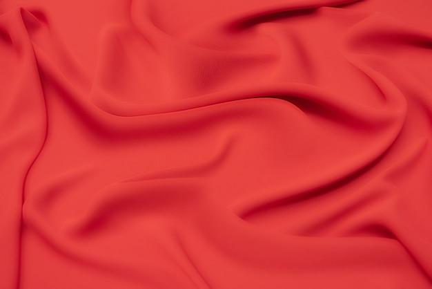Крупный план текстуры натуральной красной или оранжевой ткани или ткани того же цвета. фактура ткани из натурального хлопка, шелка или шерсти или льняного текстильного материала. красный и оранжевый фон холста.