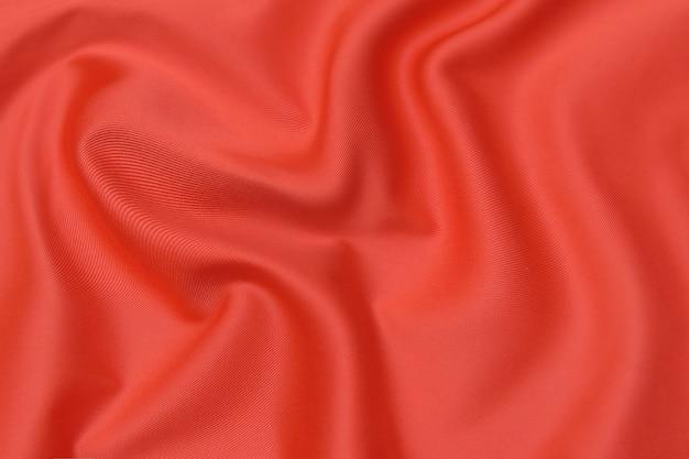 同じ色の天然の赤またはピンクの生地または布のクローズアップテクスチャ。天然コットン、シルク、ウール、またはリネンのテキスタイル素材の生地の質感。赤とオレンジ色のキャンバスの背景。