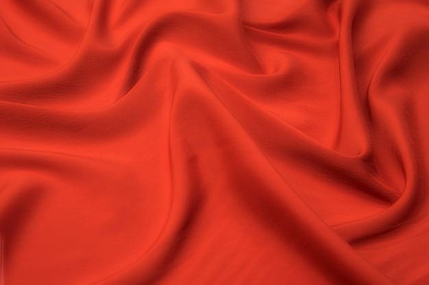 Крупный план натуральной красной или розовой ткани или ткани того же цвета. фактура ткани из натурального хлопка, шелка или шерсти или льняного текстильного материала. красный и розовый фон холст.