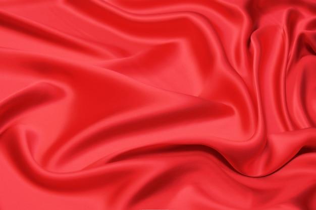 Крупный план натуральной красной или розовой ткани или ткани того же цвета. фактура ткани из натурального хлопка, шелка или шерсти или льняного текстильного материала. фон красный холст.