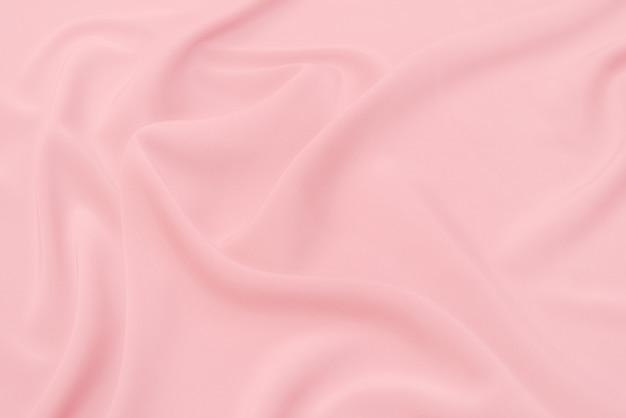 同じ色の天然の赤またはピンクの生地または布のクローズアップテクスチャ。天然コットン、シルク、ウール、またはリネンのテキスタイル素材の生地の質感。赤いキャンバスの背景。