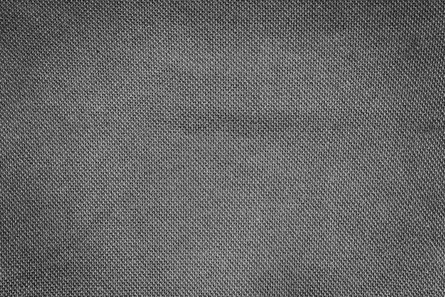 어둡고 검은색의 천연 직물 천의 클로즈업 질감. 천연 면 또는 린넨 섬유 소재의 패브릭 질감. 블랙 패브릭 넓은 배경입니다.