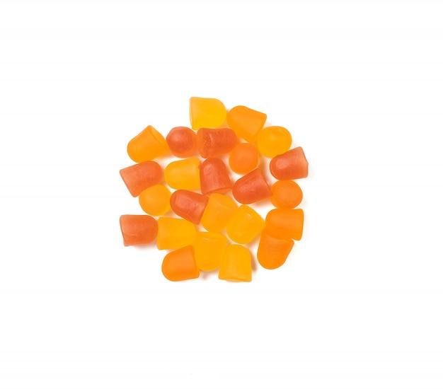 白い背景の上のオレンジと黄色のマルチビタミングミのクローズアップテクスチャ。健康的なライフスタイルのコンセプト。