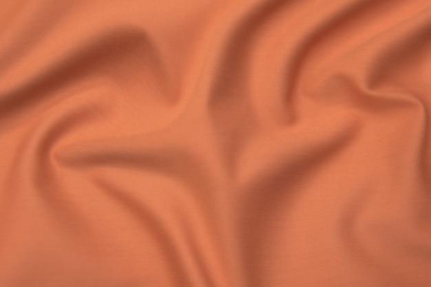 Крупный план текстуры оранжевой или коричневой ткани или ткани того же цвета. фактура ткани из натурального хлопка, шелка или шерсти или льняного текстильного материала. предпосылка холста ткани.