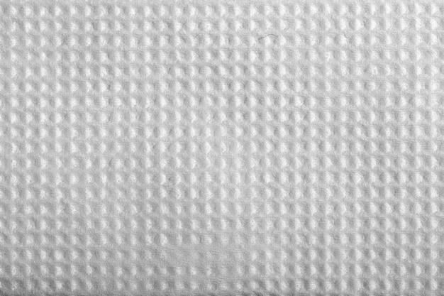 エンボス加工の正方形のホワイトペーパーナプキンのテクスチャを閉じます。