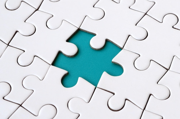 Close-up texture of a white jigsaw puzzle in assembled state with missing elements forming a blue pad for text.