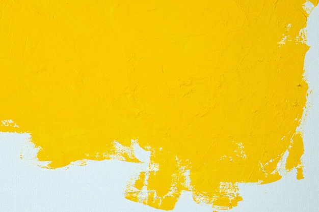 Close up texture yellow color paint on white colour canvas brush marks stroke background