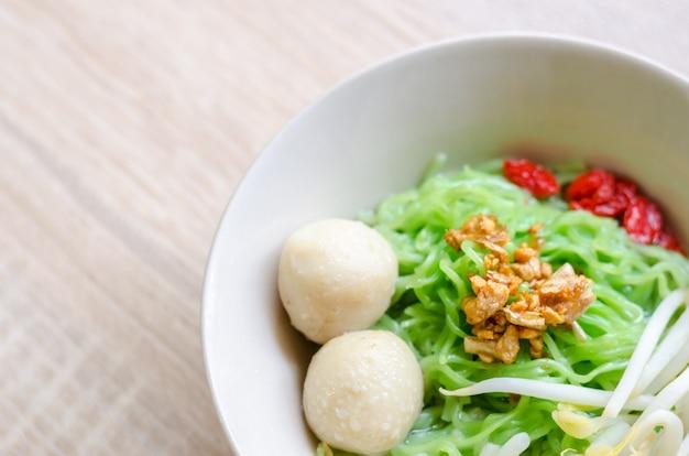 Закройте тайскую лапшу с мясным мясом и хрустящей свиной кожей на деревянном фоне. тайская еда