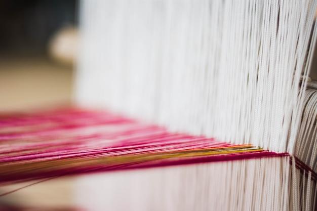 Close up of thai silk weaving on a traditional loom. close up thai silk thread.
