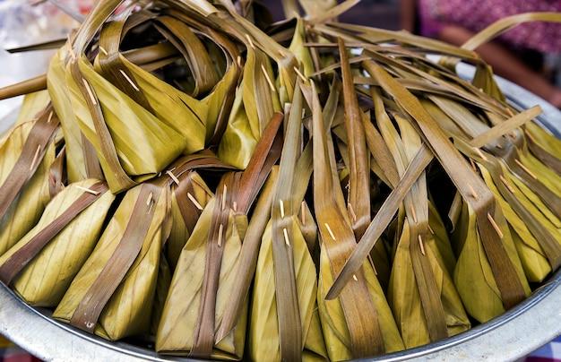 バイラーでタイの伝統的なデザート料理をクローズアップ。ココナッツもち米と甘いバナナで作った中のデザート Premium写真