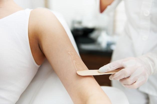 Крупный план. косметолог держит деревянную лопатку и наносит на руку женщины прозрачный гель с анестетиком, подготавливая кожу к процедуре лазерной эпиляции.