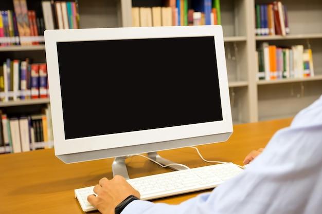机の上のコンピューターを使用している男の手でモニター画面の空白を閉じます