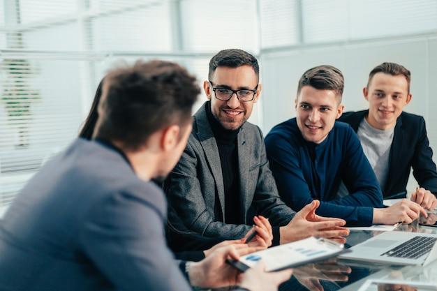閉じる。ビジネスチームは、オフィスミーティングで財務データについて話し合います。チームワーク