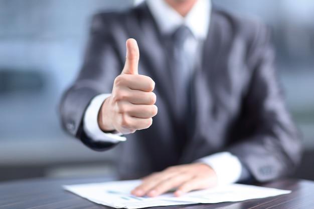 Закройте вверх. бизнесмен показывает большой палец вверх, сидя за своим столом.