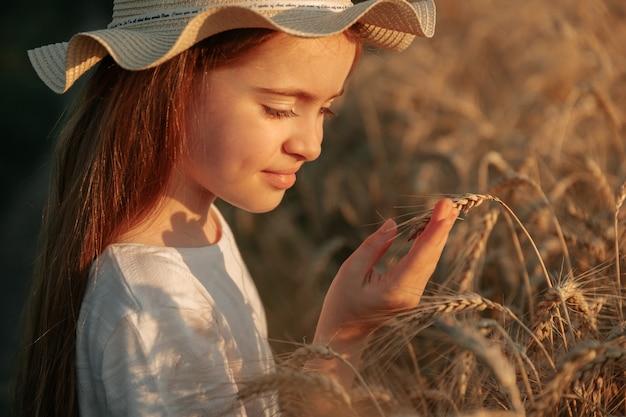 子供を閉じると、農家の娘が分析する小さな女の子の顔が小麦の金色の耳に触れます...
