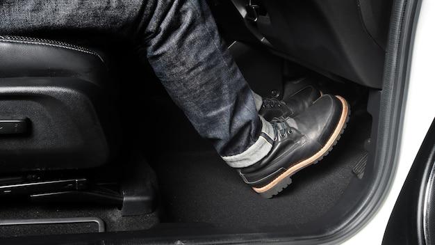 운전할 자동차의 발을 누르는 발 페달을 닫습니다. 자동차의 가속기 및 브레이크 페달. 자동차의 가속 페달을 밟고 브레이크를 밟아 자동차를 운전하는 운전자. 차량 내부. 컨트롤 페달.