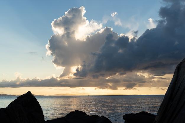 夕暮れ時にタイ海の前景の岩の正面を閉じます。
